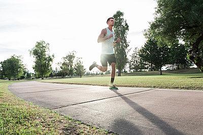 Caucasian man running on path in park - p555m1472885 by Kolostock