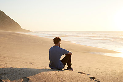 Man sitting on beach - p1124m1510938 by Willing-Holtz