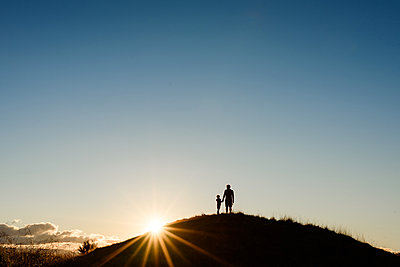 Silhouette of father and son at the top of a hill at sunset - p1166m2165975 by Cavan Images