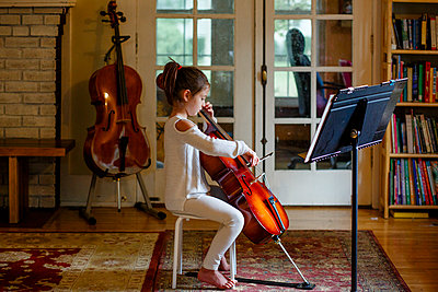a focused graceful child practices cello in window light at home - p1166m2279449 by Cavan Images