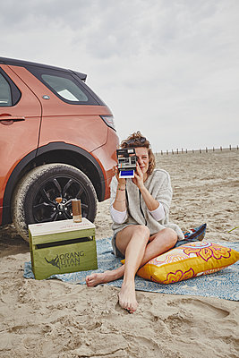 Woman with Land Rover and polaroid camera on the beach - p1573m2178924 by Christian Bendel