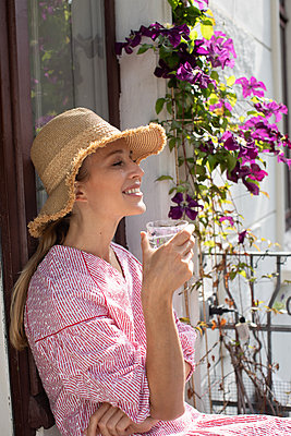 Blonde woman on her balcony - p1678m2258839 by vey Fotoproduction