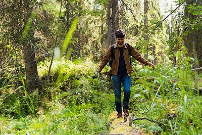 Finland, Lapland, smiling man balancing on log in forest - p300m2060758 by Kike Arnaiz