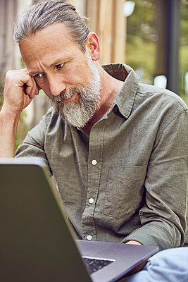 Close-up of thoughtful bearded mature man using laptop while sitting in yard - p300m2214214 by Maya Claussen