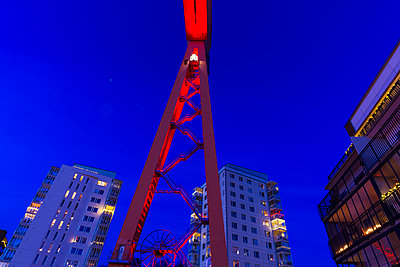 Low angle view of shipping crane, blocks of flats on background - p312m1472667 by Mikael Svensson