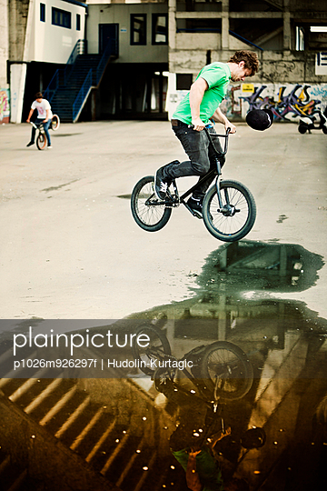 BMX biker performing a stunt over a puddle, man in background