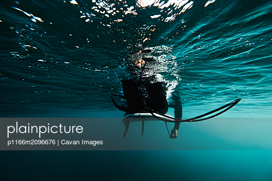 Underwater view of a surfer paddling on his surfboard - p1166m2096676 by Cavan Images