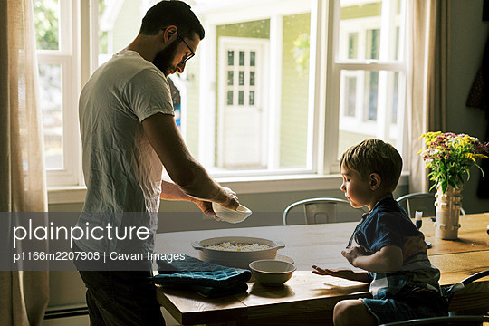 A father and son putting streusel on a peach cobbler - p1166m2207908 by Cavan Images