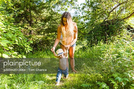 Mother helping baby boy to walk - p300m2013064 von Tom Chance