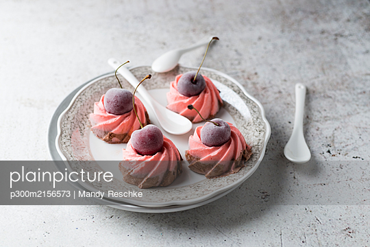 Plate of homemade ice cream tarts with chocolate and cherry on top - p300m2156573 by Mandy Reschke