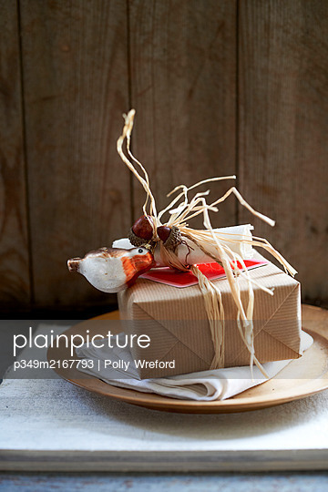 Gift wrapped in brown paper with string and robin ornament - p349m2167793 by Polly Wreford
