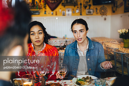 Young women talking with male friend during dinner party at restaurant - p426m2046313 by Maskot