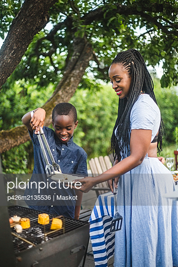 Smiling son assisting mother in preparing food at barbecue grill during backyard party - p426m2135536 by Maskot