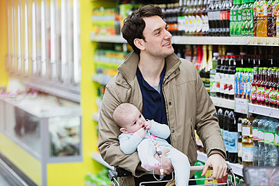 Father with baby daughter shopping in supermarket - p1023m2187677 by Sam Edwards