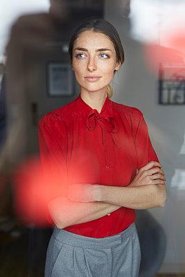 Portrait of woman wearing red blouse standing behind windowpane - p300m1581274 von Philipp Nemenz