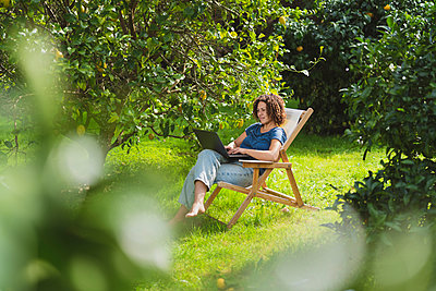 Mid adult woman using laptop while sitting on chair amidst trees in garden - p300m2268094 by Steve Brookland