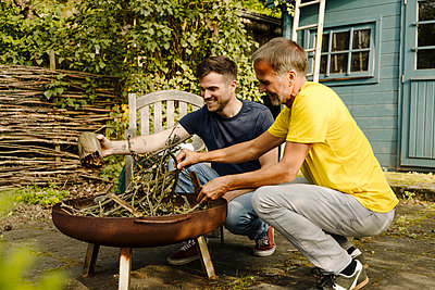 Smiling father and son doing preparation of fire pit in back yard - p300m2275025 by Gustafsson