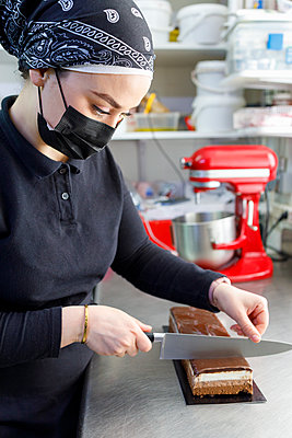 Female owner cutting slice of cake in bakery - p300m2281884 by Ignacio Ferrándiz Roig