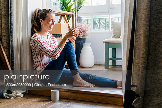 Smiling woman sitting on the floor at home with cell phone - p300m2080099 by Giorgio Fochesato