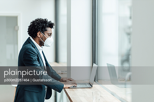 Mature businessman wearing protective face mask using laptop in office during COVID-19 - p300m2287464 by Gustafsson