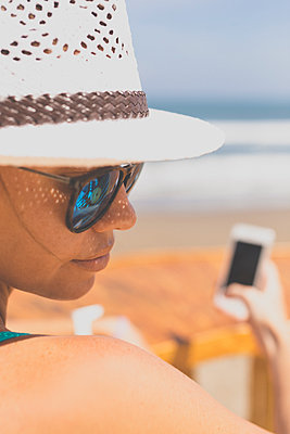 Young woman in sunglasses with phone - p1108m1158927 by trubavin