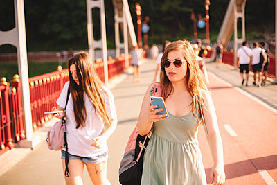Two young women using smart phones walking on bridge in summer - p1166m2212440 by Cavan Images