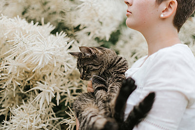 Teenage girl carries a cat in her arms - p1507m2172007 by Emma Grann