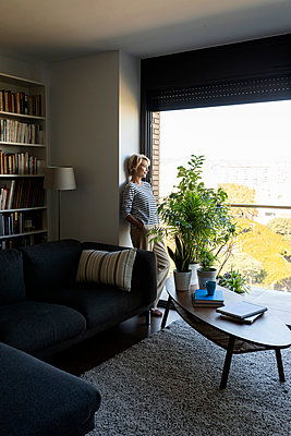 Mature woman standing at the window in living room at home looking out - p300m2144944 by Valentina Barreto