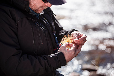 Fisherman tying fly on fishing line while standing in river at forest - p300m2213945 by Studio 27