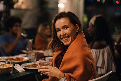 Portrait of smiling young woman holding drink while sitting at table during dinner party in backyard - p426m2046188 by Maskot