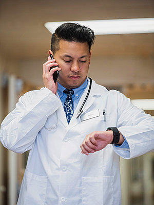 Filipino doctor talking on cell phone and checking the time - p555m1521389 by Erik Isakson