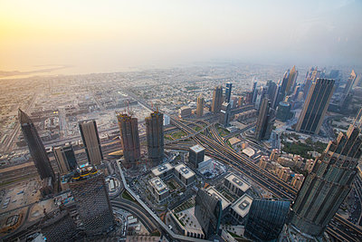 Aerial view of cityscape against sky during sunrise from Burj Khalifa - p1166m1489900 by Cavan Images
