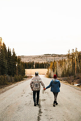Couple holding hands, walking down remote, rural road - p1192m2094309 by Hero Images