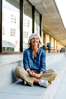 Mature businesswoman sitting cross-legged on steps in the city, using smartphone - p300m2156681 by Sofie Delauw