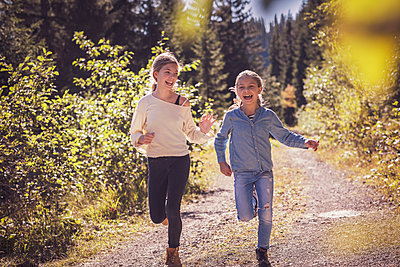 Girls running and having fun on a forest path in the countryside - p300m2166383 by Studio 27