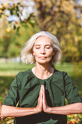 Woman sitting with hands clasped while doing yoga at park - p300m2226640 by Katharina und Ekaterina