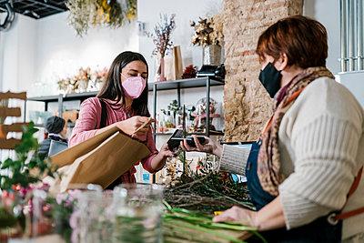 Valencia, Spain. Woman buying flowers in a florist's shop, paying by credit card. - p300m2274946 von Ezequiel Giménez