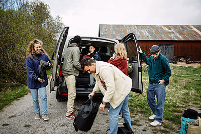 Happy male and female friends removing backpacks from car trunk against sky - p426m2117223 by Maskot