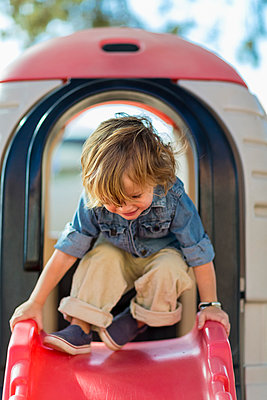Caucasian boy playing at playground - p555m1410480 by Marc Romanelli