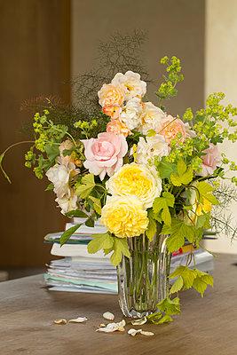 Glasvase auf Tisch mit Rosenstrauß in Pastellfarben - p948m2134093 von Sibylle Pietrek