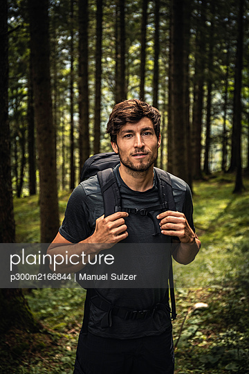 Portrait of a man with backpack on a hiking trip in forest, Karwendel, Tyrol, Austria - p300m2166844 by Manuel Sulzer