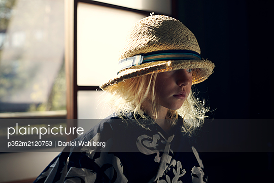 Girl wearing straw hat by window - p352m2120753 by Daniel Wahlberg
