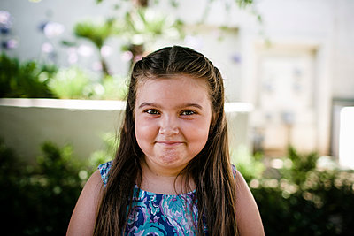 Portrait of cute girl smiling while standing at park - p1166m2025201 by Cavan Images
