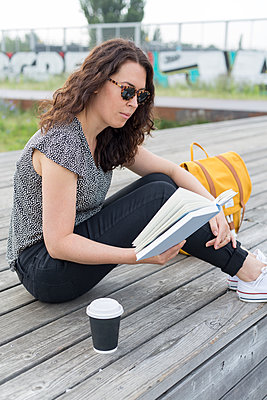 Junge Frau liest ein Buch im Park - p1396m1464949 von Hartmann + Beese
