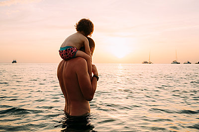 Back view of father carrying his little daughter on shoulders in the sea watching sunset - p300m1587241 von Gemma Ferrando