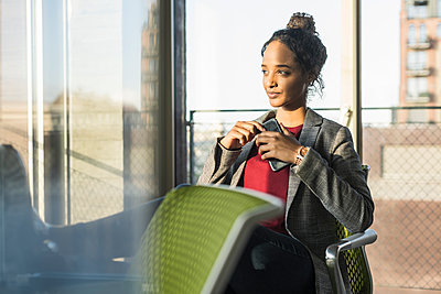 Young businesswoman with cell phone sitting at the window in office - p300m2160323 by Uwe Umstätter