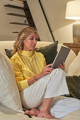 Mature woman using digital tablet while siting on lounge chair at home - p300m2241826 by Veam