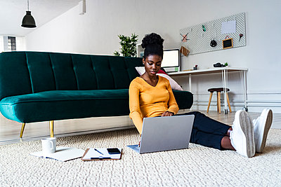 Young Afro woman using laptop while sitting on carpet against sofa in living room at home - p300m2251993 by Giorgio Fochesato