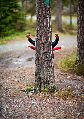 Children behind tree - p312m1139522 by Peter Rutherhagen