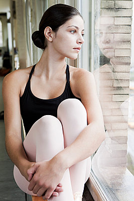 Ballerina looking through window - p9245526f by Image Source